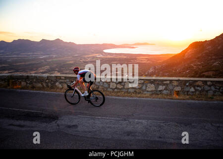 Man Radfahren auf Mountain Road bei Sonnenuntergang, Korsika, Frankreich - Stockfoto