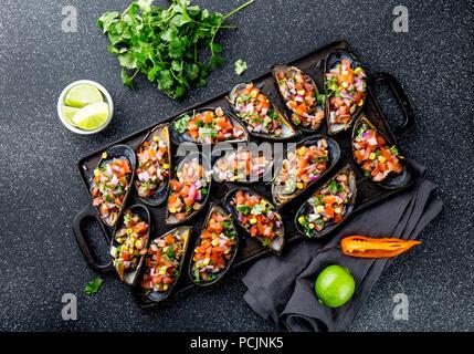 Peruanisches Essen. Choros a la chalaca. Große Muscheln, Choros zapatos gewürzt mit lila Zwiebeln, Tomaten, Mais und Zitrone. Ansicht von oben, schwarzen Hintergrund. Die peruanische Gericht - Stockfoto