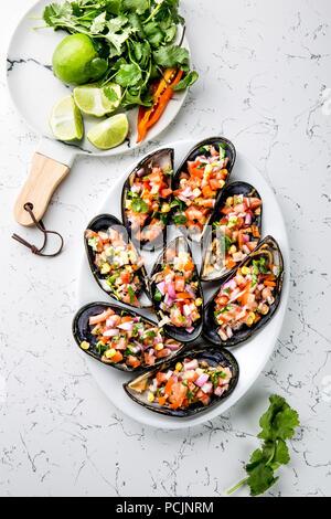 Peruanisches Essen. Choros a la chalaca. Große Muscheln, Choros zapatos gewürzt mit lila Zwiebeln, Tomaten, Mais und Zitrone. Ansicht von oben, weißen Hintergrund. Die peruanische Gericht - Stockfoto