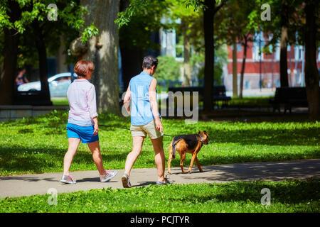 Zwei Frauen gehen in den Park mit einem Hund an einem sonnigen Tag. Park La Fontaine, Montreal, Kanada. - Stockfoto