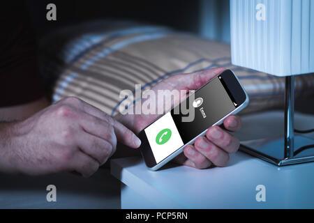 Anruf mitten in der Nacht. Betrunken oder Streich Berufung ex Freundin mit Smartphone im Schlafzimmer. Liebe Beichte. - Stockfoto