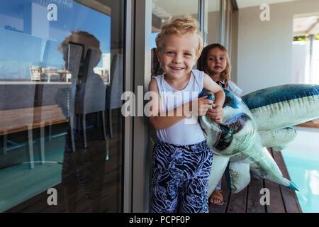 Portrait von niedlichen kleinen Jungen und seiner Schwester spielen Mit einem Hai Spielzeug in der Nähe von Schwimmbad. Kinder spielen am Pool mit aufblasbarem Spielzeug. - Stockfoto