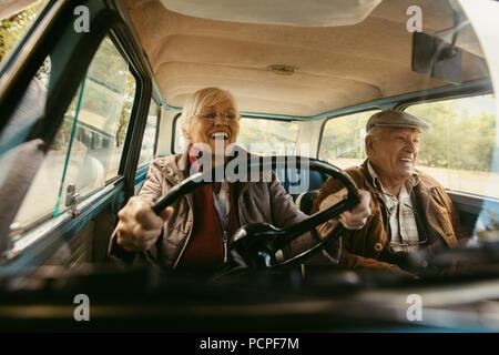 Freundliche alte Paar Fahren in einem Auto. Genießen road trip. Senior woman-driving-Auto mit Frau genießt die Fahrt und Lachen. - Stockfoto