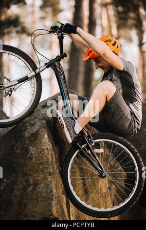 Junge Trial Biker Klettern in Fels mit Fahrrad im Freien - Stockfoto
