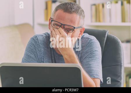 Müde Freiberufler Mann rieb seine Augen während der Arbeit mit dem Laptop - Stockfoto