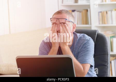 Müde Freiberufler Mann reibt sein Auge während der Arbeit mit dem Laptop - Stockfoto