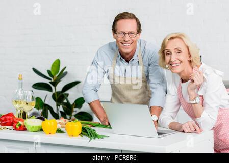 Senior Paar kochen und mit Laptop für Rezepte in der Küche - Stockfoto
