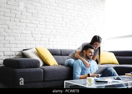 Junge hispanic Paar auf der Couch zu Hause sitzen, mit einem Tablet-PC für Internet und Social Media. Das Mädchen ist eine Massage zu ihrem Freund. Kopieren s - Stockfoto