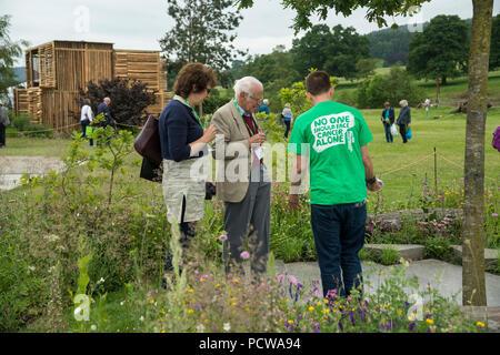 Menschen sehen zentrales Merkmal Baum, gepflasterten Bereich und Blumen im Garten, schöne Show - Macmillan Erbe Garten, RHS Chatsworth Flower Show, England, UK. - Stockfoto