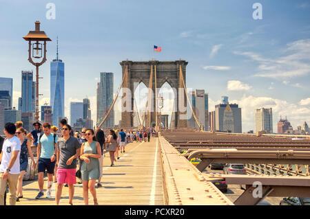 Juni 10, 2017. New York City, New York. Touristen und Verkehr auf der Brooklyn Bridge und die Skyline von New York City an einem sonnigen Tag im Sommer. - Stockfoto