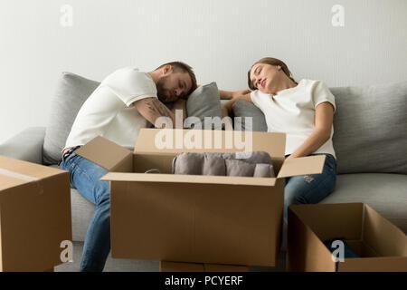 Müde junge Paar entspannt auf einem Sofa Umzug in neues Haus - Stockfoto