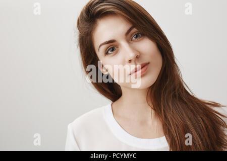 Man kann in ihren Augen ertrinken. Portrait von wunderschönen natürlichen brunette Neigekopf beim Hören mit Interesse, durch Lautsprecher charmed, an der Kamera mit Blick - Stockfoto