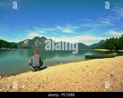 Mann sitzt auf der Steinernen Bank von alpinen See bei verankert laminierte Boot. - Stockfoto