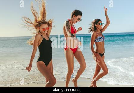 Gerne Frauen im Urlaub Sonnenbaden und genießen am Strand mit Blick auf das Meer im Hintergrund. Drei Freundinnen in Bikini tragen Sonnenbrillen tanzen und in - Stockfoto