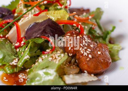 Schüssel Salat mit Rindfleisch teriyaki und Gemüse. Asiatische Küche. Salat auf einem weißen Teller am Tisch. Restaurant Menü - Stockfoto