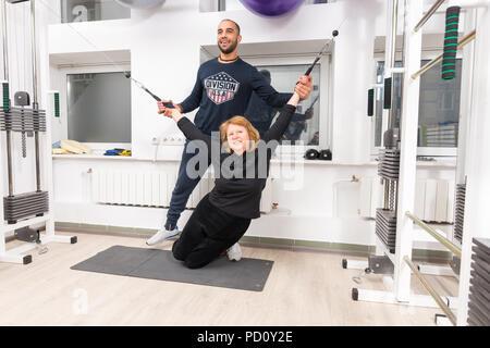 Lächelnd männlichen Trainer helfen Frau halten die Gurte an weightlifting Maschine für physikalische Therapie angeschlossen - Stockfoto