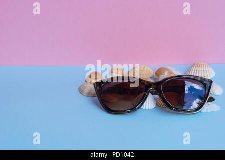 Verschiedene Arten von Muscheln und eine Sonnenbrille auf Hellblau und Rosa Hintergrund. Minimalistisches Bild, das Erfassen der Geist der Sommer. Acanthocardia Rohr - Stockfoto