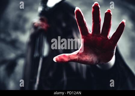 Hexe, die blutige Hand mit Reaper. Weiblicher Dämon Engel in schwarzer Kleidung und Haube auf grunge Wand Hintergrund. Halloween Tag und Geheimnis, das Konzept. Fant - Stockfoto