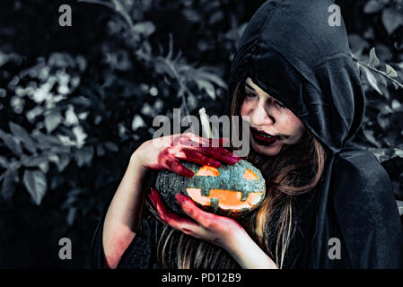 Daemon Hexe sorgen für Kürbis im Geheimnis Wald. Geist und Horror Konzept. Halloween Tag Thema. Rotes Blut auf Hexe Hände. - Stockfoto