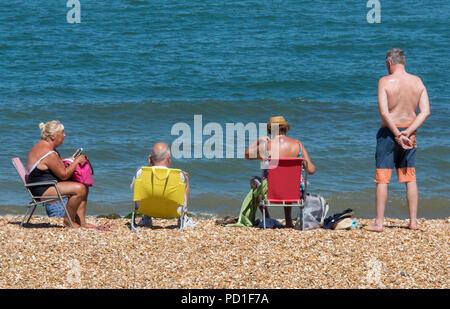 Isle of Wight, Großbritannien. 5. August 2018. Die BRITISCHE Hitzewelle und heißem Wetter weiterhin in Cowes auf der Isle of Wight mit Zuschauer genießen die warme Sonne und Blick auf den Strand von Yacht Racing und Segelregatta. Sonnenbaden auf thr Beach in das warme Wetter und Sonnenschein, Urlauber auf der Insel Wight die anhaltend hohen Temperaturen und Sonnenschein am Strand am Meer machen. Sonnenbaden und Solarium sitzen im heißen Sommer Sonne am Strand. Quelle: Steve Hawkins Fotografie/Alamy leben Nachrichten - Stockfoto