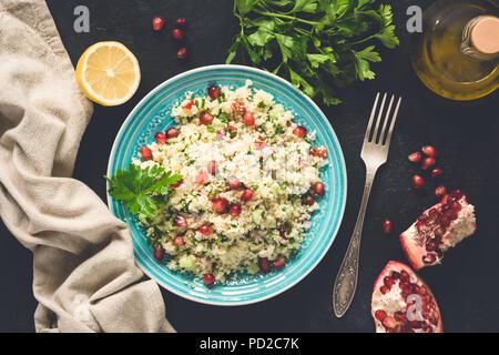 Im Nahen und Mittleren Osten Salat Tabbouleh mit CousCous, Granatapfel Samen, Petersilie. Ansicht von oben, getönten Bild - Stockfoto