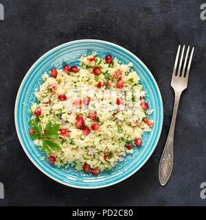 Tabbouleh Salat mit Couscous und Granatapfel Samen auf einem blauen Schild auf schwarzem Stein. Ansicht von oben, Quadrat Erntegut - Stockfoto