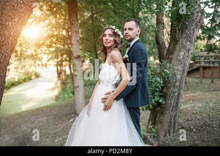 Braut und Bräutigam am Hochzeitstag zu Fuß im Freien auf Sommer Natur. Brautpaar, gerne frisch verheiratete Frau und Mann umarmen im Green Park. Liebe Hochzeit - Stockfoto