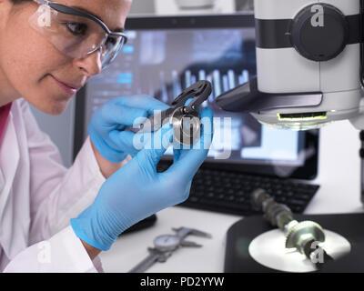 Ingenieur Maßnahmen hergestellt Komponente für Genauigkeit und Qualität Kontrolle mit Schieblehre, 3D Stereo Mikroskop im Hintergrund - Stockfoto