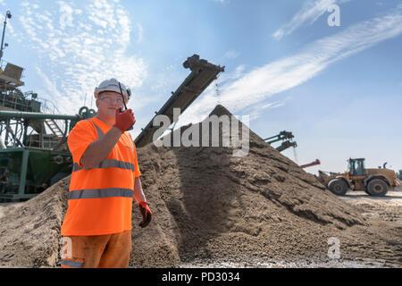 Mitarbeiter sprechen über Walkie talkie mit Brecher und konkrete Siebmaschine in Beton recycling Site - Stockfoto