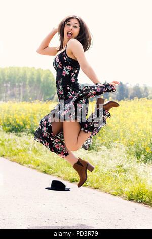 Volle Länge Aktion Portrait von jungen Mädchen in Flower dress springen im Freien. - Stockfoto