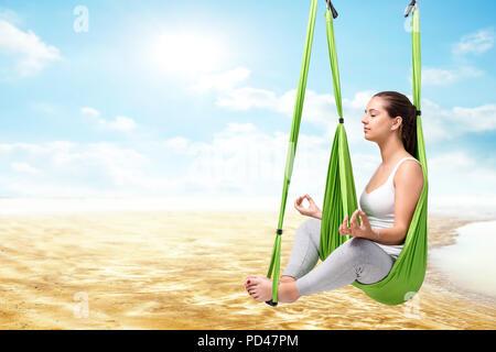 Konzeptionelle Porträt der jungen Frau in Antigravity yoga Hängematte sitzen mit geschlossenen Augen. Mädchen tun geistliche Übung gegen Flussbett und blauer Himmel. - Stockfoto