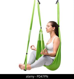 Porträt der jungen Frau zu tun Antenne Yoga. Mädchen sitzend mit Augen in Grün antigravity yoga Hängematte geschlossen auf weißem Hintergrund. - Stockfoto