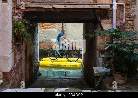 Ein Mann auf einer Überschwemmung Fahrrad segeln auf einem Kanal in Venedig. - Stockfoto