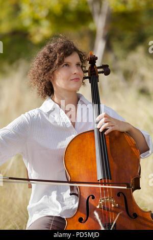 Frau spielt das Cello zwischen Feldern - Stockfoto
