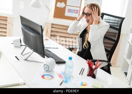 Ein junges Mädchen sitzt an einem Tisch im Büro, die Hände hinter dem Kopf und Blick auf den Monitor. - Stockfoto