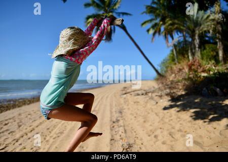 Ein junges Mädchen, das Schwingen von Seil an einem tropischen Strand, Küste Szenen aus den tropischen Norden von Queensland, Toolakea QLD, Australia - Stockfoto