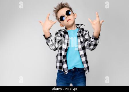 Blaues T-Shirt und Jeans steht auf einem grauen Hintergrund. Der Junge trägt runden Brille. Rothaarige junge zeigt ein Rocker Ziege - Stockfoto