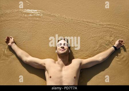 Zufrieden gebräunte Mann mit geschlossenen Augen liegt mit ausgestreckten Armen auf dem Sand Strand im Freien. Die Sonne scheint auf seinem Körper. Er trägt weiße Wireless earpho - Stockfoto