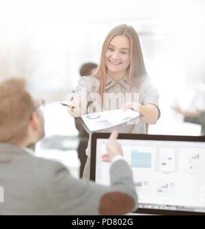 Weibliche Assistant gibt dem Mitarbeiter eine finanzielle Dokument. Büro werktags - Stockfoto