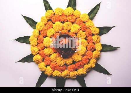 Blume Rangoli für Diwali oder Pongal Festival hergestellt mit Marigold oder Zendu Blumen und Mangoblatt und Ton Öl Lampe auf weißem Hintergrund, selektiv fo
