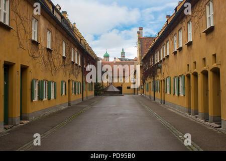 Fuggerei in Augsburg Bayern Deutschland älteste Sozialsiedlung der Welt gelb Einfache angeschlossenen Häuser gespendet von Jakob Fugger - Stockfoto