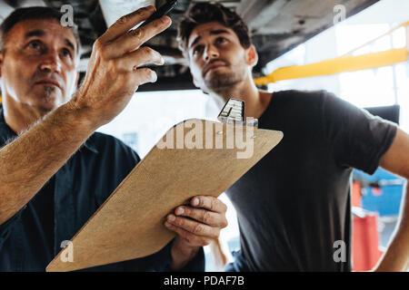 Zwei erfahrene Mechaniker stehen unter einem Auto und untersuchen das Problem. Mechanik, Auto Inspektion mit Zwischenablage. - Stockfoto