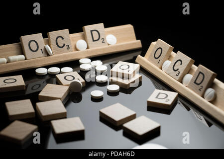 OCD Konzept in Scrabble Text mit pharmazeutischen Medikamente auf einem schwarzen Tabelle geschrieben. Zwangsstörungen und Verhalten - Stockfoto