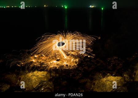Man Duschen glühende Funken von spinning Stahlwolle auf felsigen Strand bei Nacht. - Stockfoto
