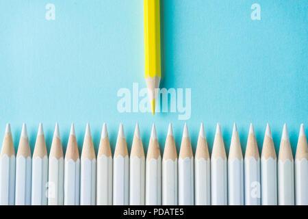 Business-Konzept - viele weiße Bleistifte und Farbstift auf blauem Papierhintergrund. Es ist Symbol für Kampf, Führung und Kommunikation. - Stockfoto