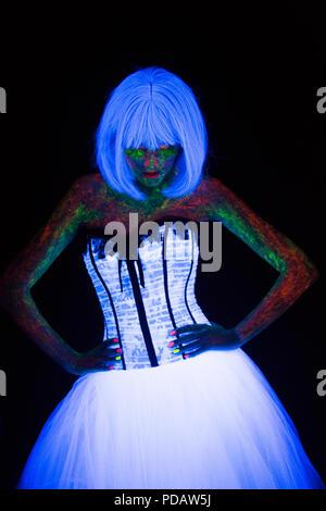 Konzept der Hochzeit Fotosession in Neon Beleuchtung in der Mode Stil Braut hält die Hände in die Taille und leuchtet im Dunkeln junges Mädchen mit Frisur Quads und Blumenstrauß im weissen Brautkleid posing unter der UV-Strahlen auf einem dunklen Hintergrund im Studio - Stockfoto