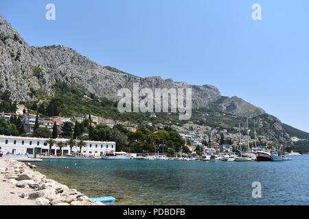 Hell Blau Sonniger Tag in Omis Kroatien mit türkisblauem Meer bergigen Umgebung und eine schöne Hafenstadt mit kleinen Hotels - Stockfoto
