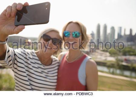 Lächelnde Mutter und Tochter unter selfie im sonnigen städtischen Park - Stockfoto