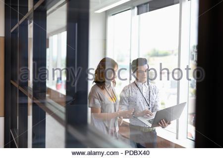 Kaufmann und Kauffrau mit Laptop im Büro Flur - Stockfoto