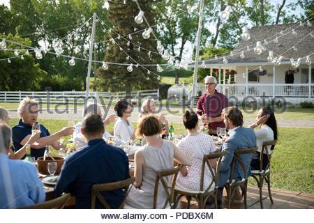 Älterer Mann, der feierliche Toast im Garden Party Tabelle - Stockfoto